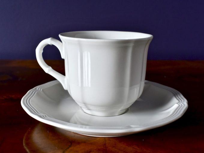 biała porcelanowa filiżanka z podstawką